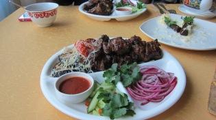 Uzbekistanilaisia herkkuja, hiiligrillissä kypsenettyä lammasta ja vihanneksia.
